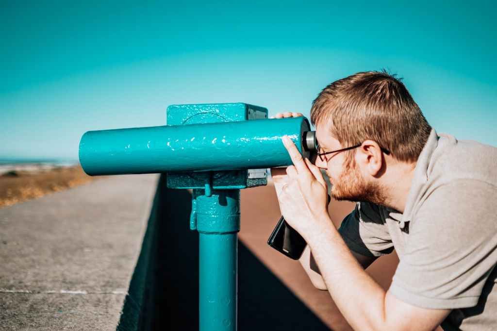 Man focusing on farther object with monocular